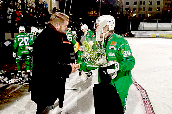 Erik Sundström på Infotiv skakar hand med en bandyspelare